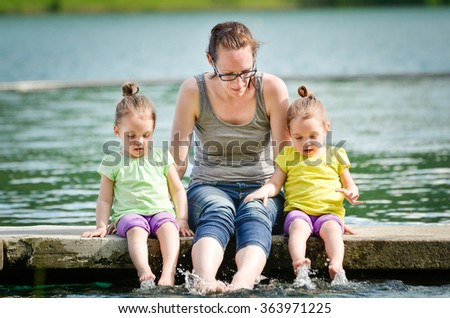 Mother and little children twin girls are playing on a lake or sea. Sitting on a pier, active family lifestyle. - stock photo