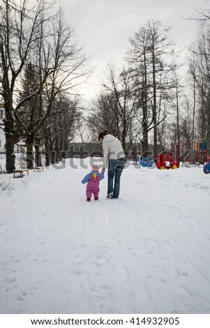 Mother and little daughter are going to the playground in winter day holding hands, they are turned backs to camera. - stock photo