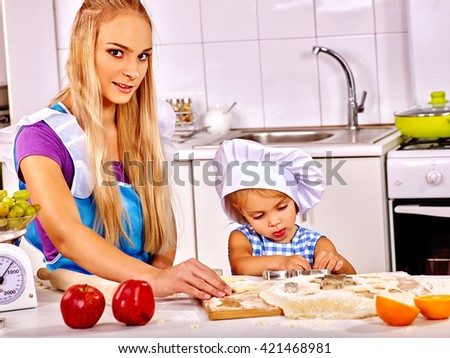 Mother and little daughter baking cookies at kitchen. Hat on head. Kitchen help concept.