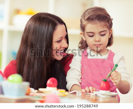 Mother and little daughter decorating Easter eggs - stock photo