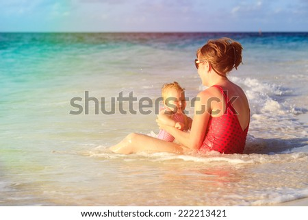 mother and little daughter having fun at sand beach - stock photo