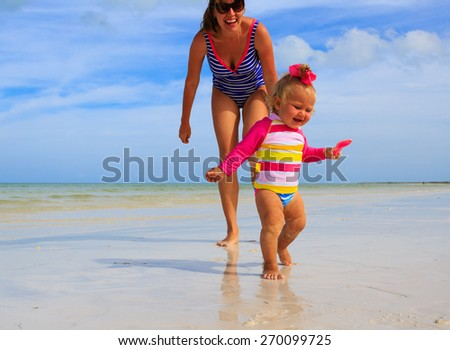 mother and little daughter having fun on summer beach - stock photo