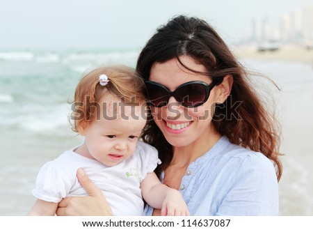 Mother and little daughter having fun on the beach