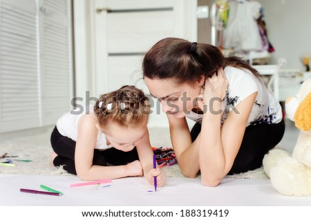 mother and little daughter having fun painting pictures - stock photo