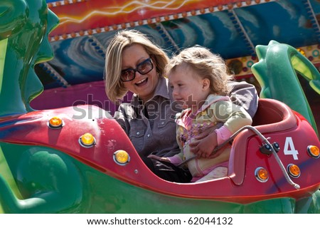 Mother and little daughter having fun rinding on carousel.