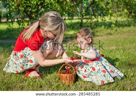 Mother and little daughter in garden with basket  cherries. Sunny summer day.