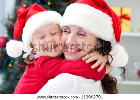 Mother and little daughter in santa suit holding in Christmas day - stock photo