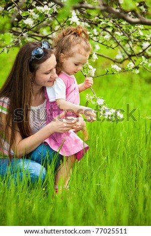 Mother and little daughter in the garden - stock photo