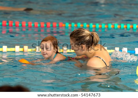 mother and little daughter in the pool - stock photo