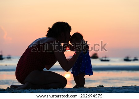 mother and little daughter on sunset beach - stock photo