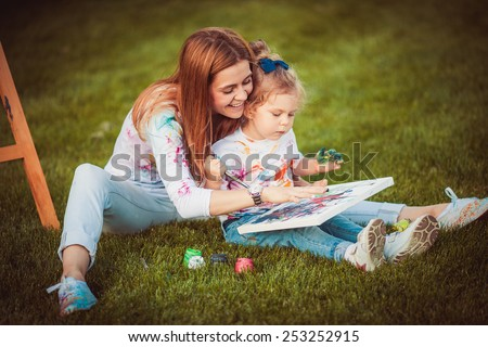Mother and little daughter paint together outdoors - stock photo