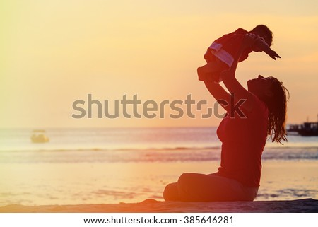 mother and little daughter play at sunset - stock photo