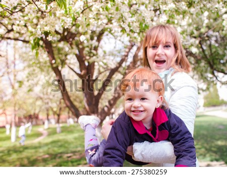 Mother and little daughter play in the summer in the Park