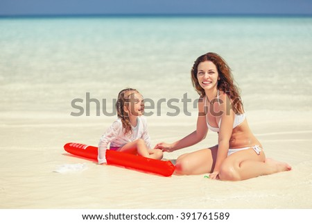 Mother and little daughter playing on the beach - stock photo