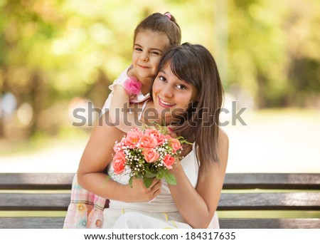 Mother and little daughter portrait in a park. - stock photo