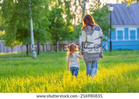Mother and little daughter walking in spring sunny park - stock photo