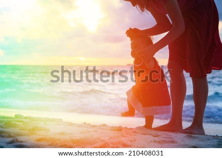 mother and little daughter walking on sand beach at sunset - stock photo