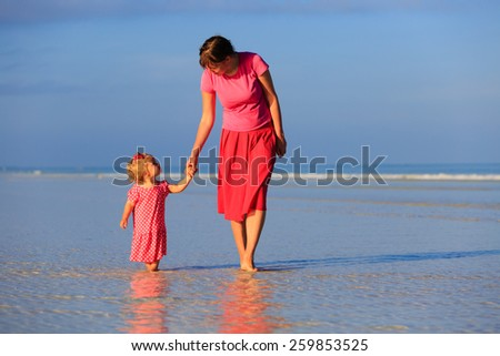 mother and little daughter walking on summer beach - stock photo