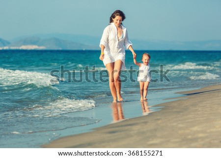 Mother and little daughter walking on the beach - stock photo