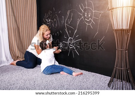 mother and little daughter with flowers. Close Up Of Affectionate Mother And Daughter At Home  - stock photo