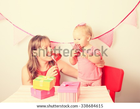 mother and little daughter with lollipops on birthday party - stock photo