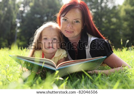 Mother and little girl reading book
