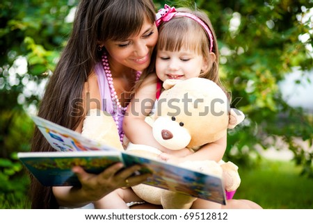 Mother and little girl reading book together - stock photo
