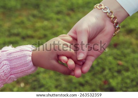 Mother and little girl's hands in green garden - vintage. - stock photo