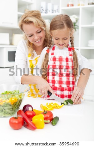 Mother and little girl slicing vegetables in the kitchen preparing a salad