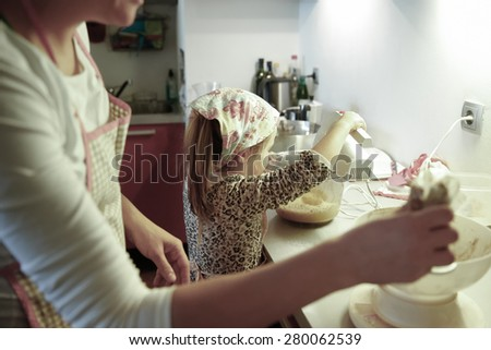 Mother and little girl spending quality time together in the kitchen, weighing and mixing ingredients for birthday cake, having fun. Family values, learning through inclusion concept.  - stock photo