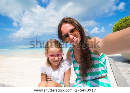 Mother and little girl taking selfie at tropical beach - stock photo