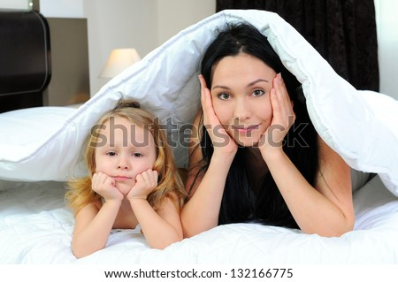 Mother and little girl under the quilt having quality time together - stock photo