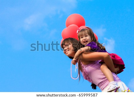 Mother and little girl with balloons - stock photo