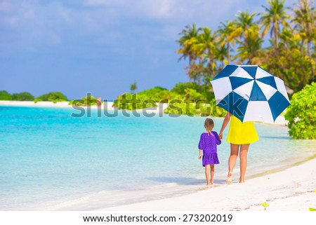 Mother and little girl with umbrella hiding from sun at beach