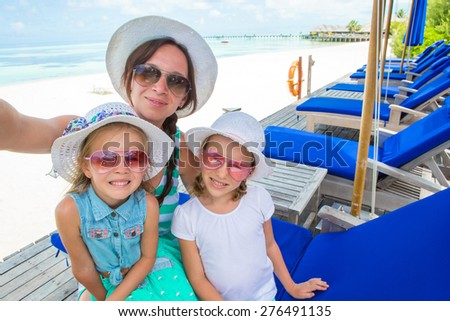 Mother and little girls taking selfie at tropical beach - stock photo