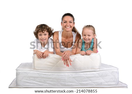 Mother and little kids sitting on a lot of mattresses, isolated on white background - stock photo