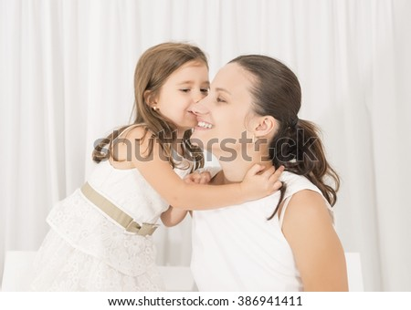 Mother and little lovely daughter. Beautiful little girl embracing and kissing her mother on white background. Happy family concept. Mothers day - stock photo