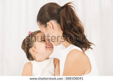Mother and little lovely daughter. Mother embracing and kissing her beautiful little girl on white background. Happy family concept. Mothers day - stock photo