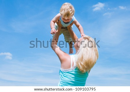 Mother and little son  against blue sky - stock photo