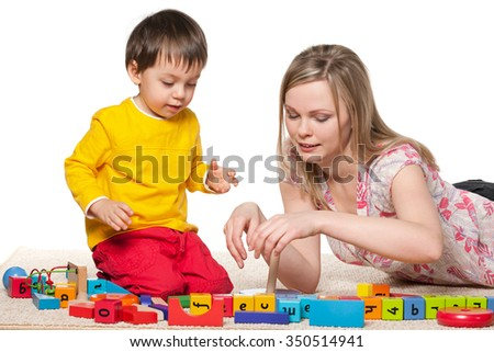 Mother and little son are playing on the carpet with blocks - stock photo