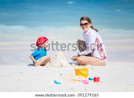 Mother and little son building a sand castle on the beach - stock photo