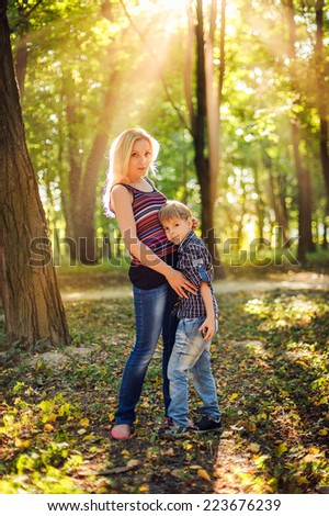 Mother and little son in park or forest, outdoors. Hugging and having fun together - stock photo