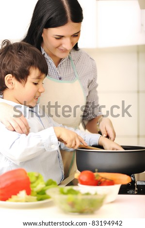 Mother and little son in the kitchen - stock photo