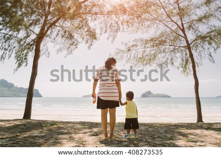 mother and little son on the beach - stock photo