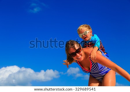 Mother and little son playing airplane on sky at beach