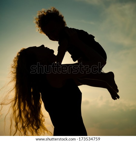 Mother and little son silhouettes on beach at sunset - stock photo
