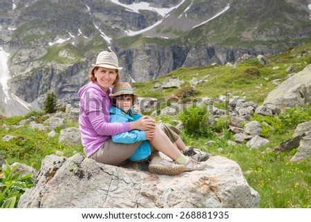 mother and little son sitting on the stone in the summer mountains