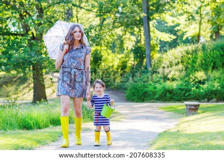 Mother and little toddler girl walking in yellow rubber boots, family look, in summer park - stock photo