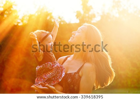 Mother and lovely daughter at sunny park. Happy family concept. - stock photo