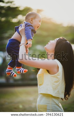 Mother and lovely son at sunny field with intentional sun glare. Happy family concept. - stock photo